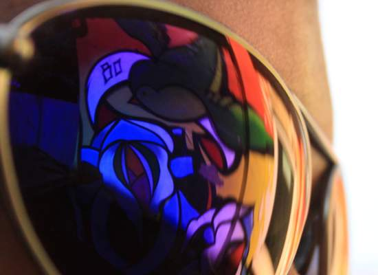 Colourful graffiti reflected in a lens.