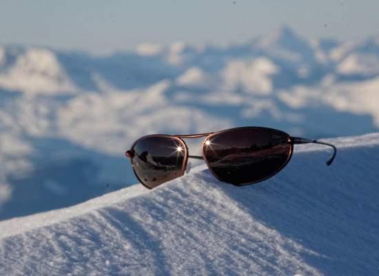 Bigatmo Exo sunglasses balanced on a snow covered ridge in a mountain range.