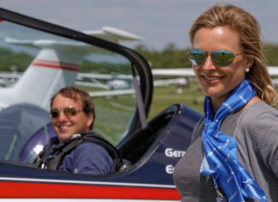 Gerald Cooper aerobatic pilot in Extra, Sarah standing beside, both wearing Bigatmo pilot sunglasses.