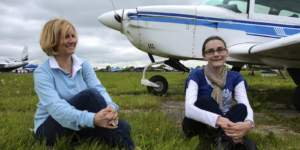 Two ladies sitting beside a small aircraft
