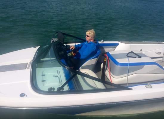 a woman in a blue jacket wearing Bigatmo sunglasses driving a speedboat