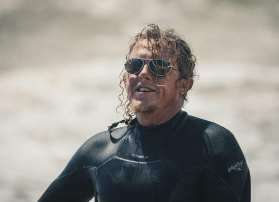 Man with long curly hair, coming out of the sea wearing a wetsuit and Bigatmo sunglasses.
