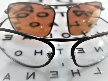 Clear and tinted prescription sunglasses sitting on an opticians eye test chart