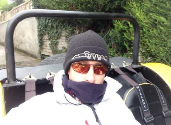 picture of a driver wearing Bigatmo sunglasses, scarf and hat, a yellow Westfield car