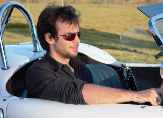 Man in Bigatmo sunglasses and black shirt driving a white A C Cobra