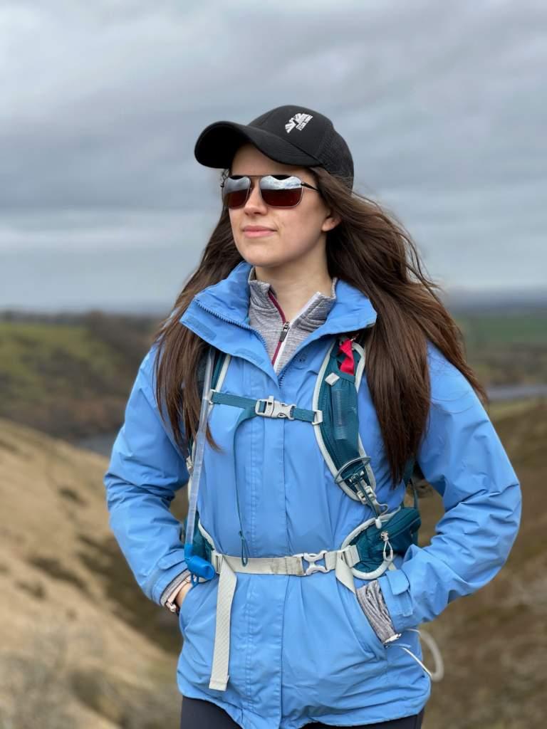 Young woman hiking in dartmoor wearing blue jacket baseball cap and Bigatmo sunglasses